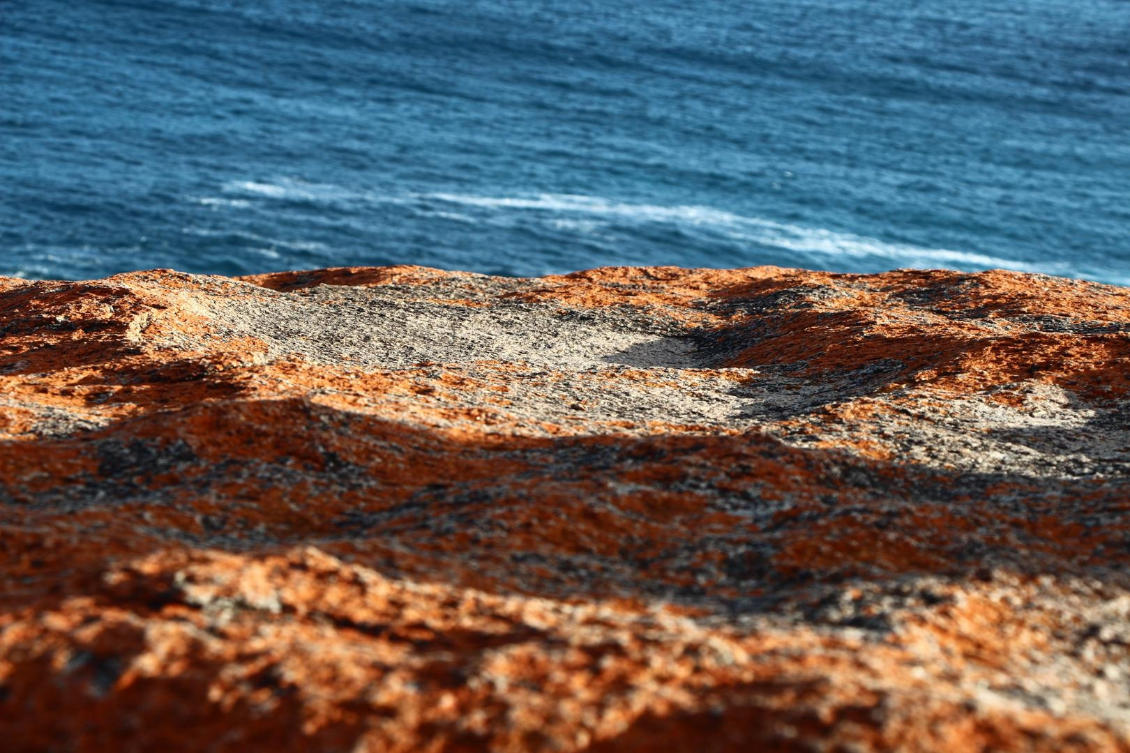 THe rocks are covered in golden-orange lichen, causing it to look yellow, orange, or red depending on the lighting.